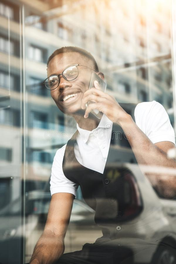 Junger AfroamerikanerGeschäftsmann in der Klage und Brillen, die am Telefon auf dem Hintergrund des Geschäftszentrums sprechen stockbilder