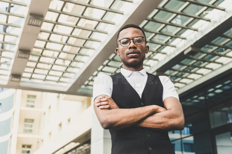 Junger AfroamerikanerGeschäftsmann in der Klage und Brillen, die am Telefon auf dem Hintergrund des Geschäftszentrums sprechen stockfotografie