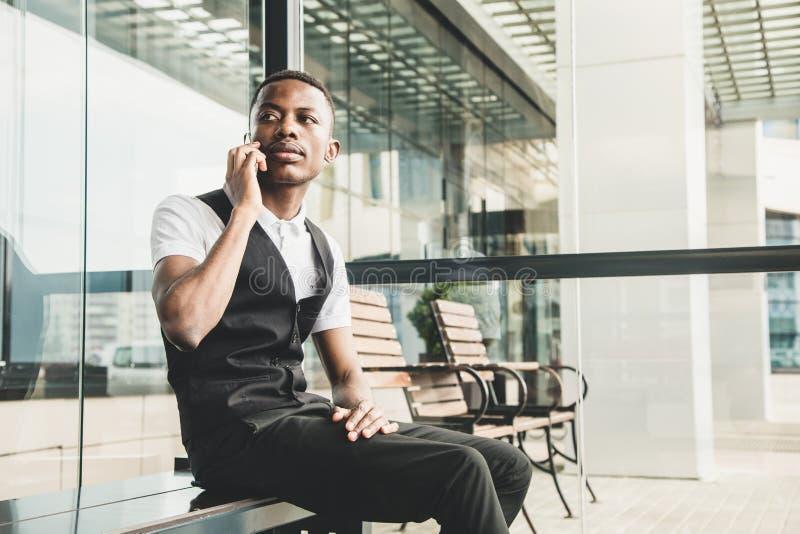 Junger AfroamerikanerGeschäftsmann in der Klage und Brillen, die am Telefon auf dem Hintergrund des Geschäftszentrums sprechen stockfoto