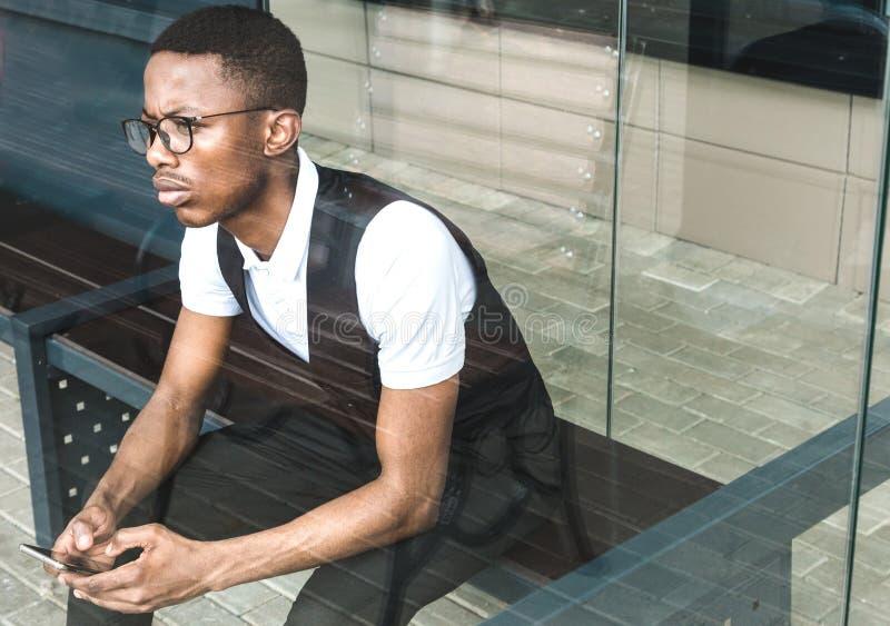 Junger AfroamerikanerGeschäftsmann in der Klage und Brillen, die am Telefon auf dem Hintergrund des Geschäftszentrums sprechen lizenzfreies stockbild