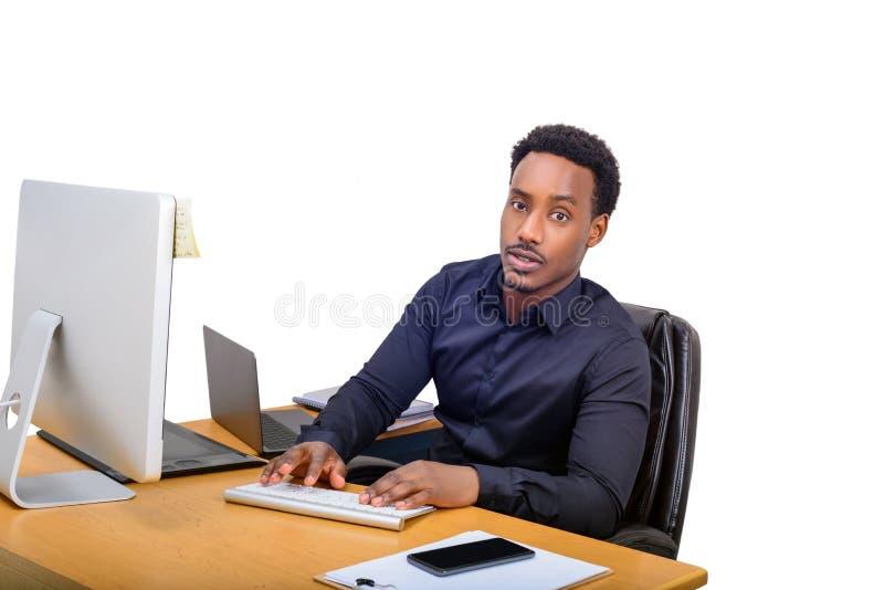 Junger AfroamerikanerGeschäftsmann, der an seinem Schreibtisch sitzt und auf Computer schreibt lizenzfreie stockfotografie