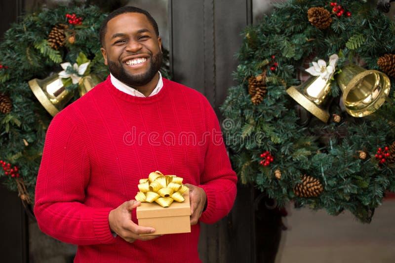 Junger Afroamerikanermann, der ein Geschenk hält lizenzfreies stockfoto
