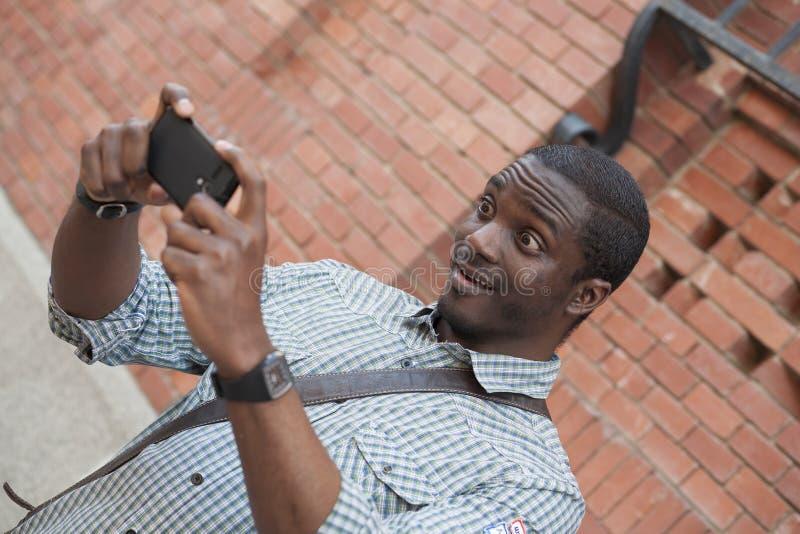 Junger Afroamerikanermann, der Selbstporträt mit beweglichem Phon nimmt lizenzfreie stockbilder