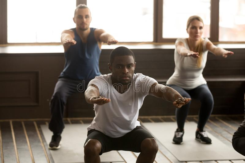 Junger Afroamerikanermann, der untersetzte Übungen an Gruppe fitnes tut lizenzfreie stockfotos