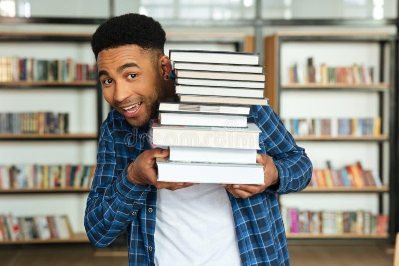 Junger afroer-amerikanisch Holdingstapel des männlichen Studenten Bücher lizenzfreies stockbild
