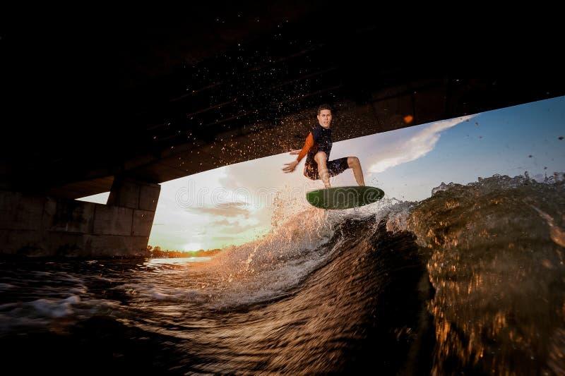 Junger aktiver Mann, der auf das wakeboard unter die Brücke springt stockbild
