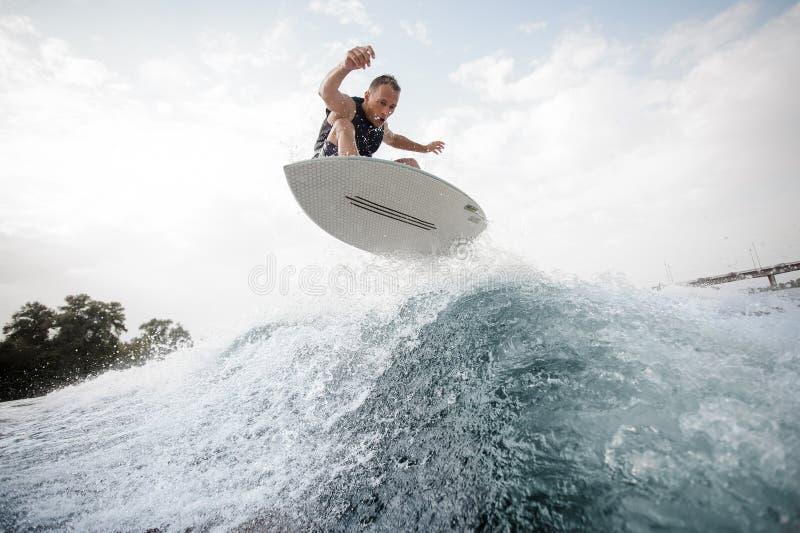 Junger aktiver Mann, der Sprung auf dem weißen wakeboard auf dem Blau macht stockfoto