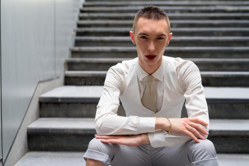 Junger androgynischer homosexueller LGTB-Geschäftsmann, der auf Treppe sitzt stockbild