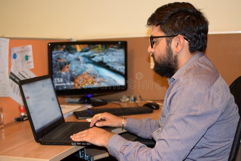 Junger Angestellter, der an Laptop während der Büroarbeitszeit im Büro arbeitet lizenzfreies stockfoto