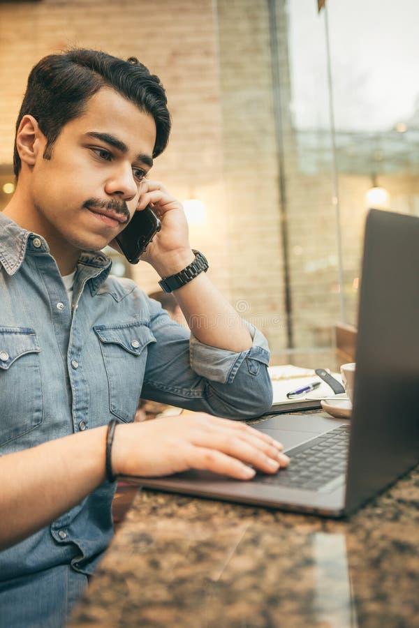 Junger arabischer Geschäftsmann, der im Café unter Verwendung des Telefons und des Computers arbeitet Moderner Großstadtlebenssti lizenzfreie stockfotos