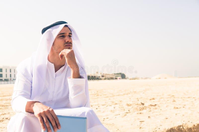 Junger arabischer Mann, der am Strand sitzt stockfoto