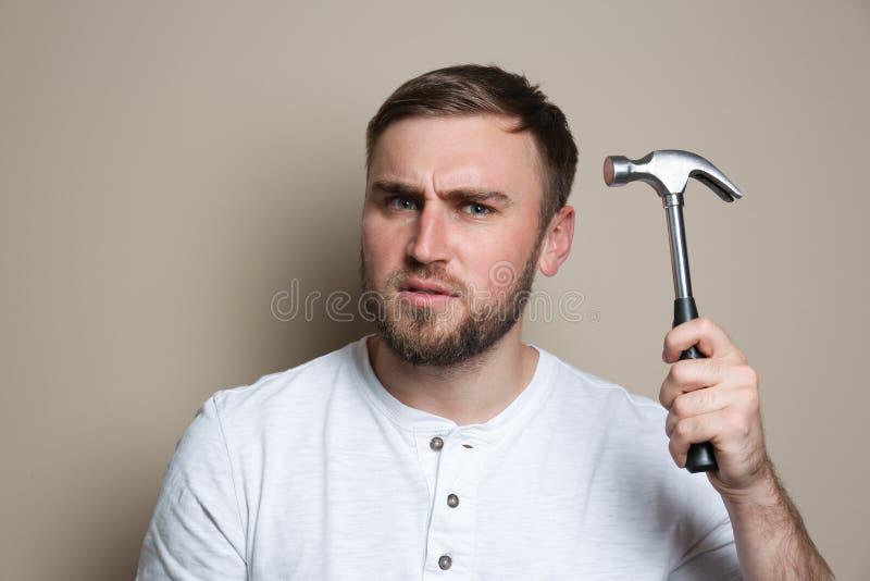 Junger Arbeiter mit Hammer auf Beige stockfotos