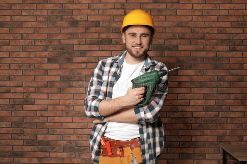 Junger Arbeiter mit moderner elektrischer Bohrmaschine lizenzfreie stockfotos