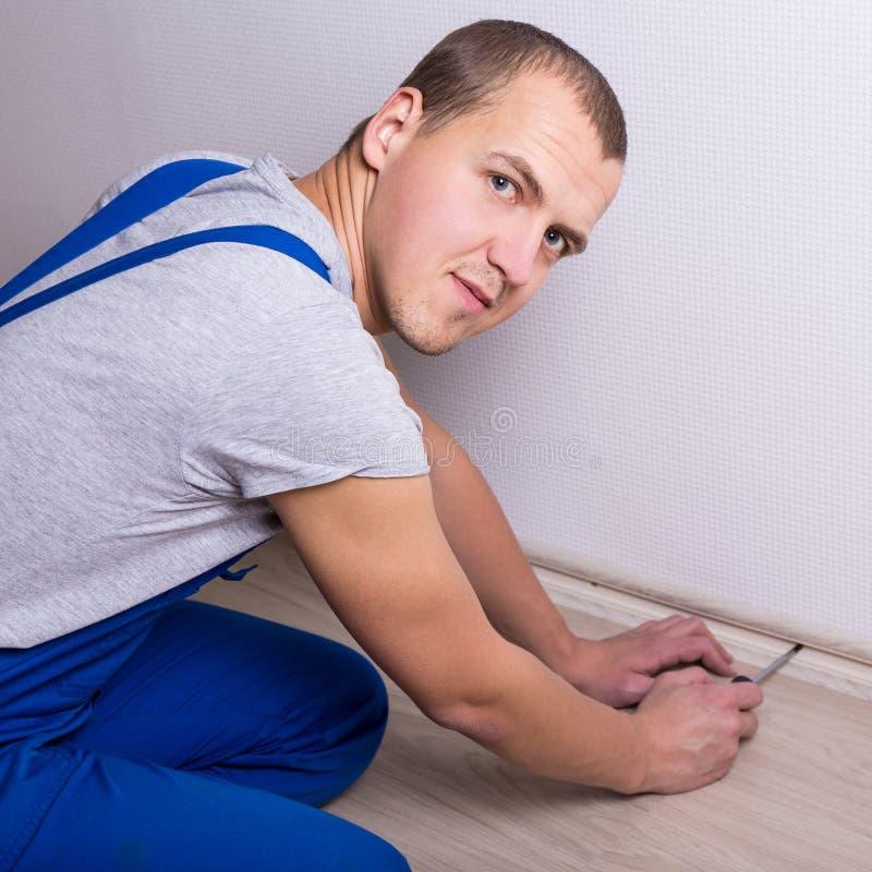 Junger Arbeitnehmer, der zu Hause neue Fussleiste installiert lizenzfreies stockbild