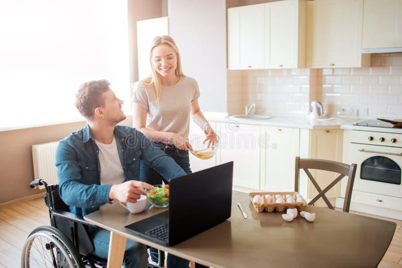 Junger Arbeitnehmer sitzen auf Rollstuhl und Blick an der Frau Er arbeitet mit Laptop und isst Salat Sie betrachten einander und  stockfoto