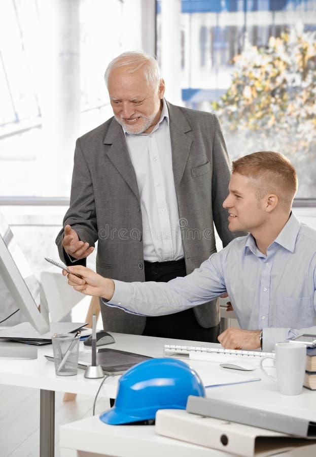 Junger Architekt, der Arbeit mit Chef behandelt lizenzfreies stockfoto