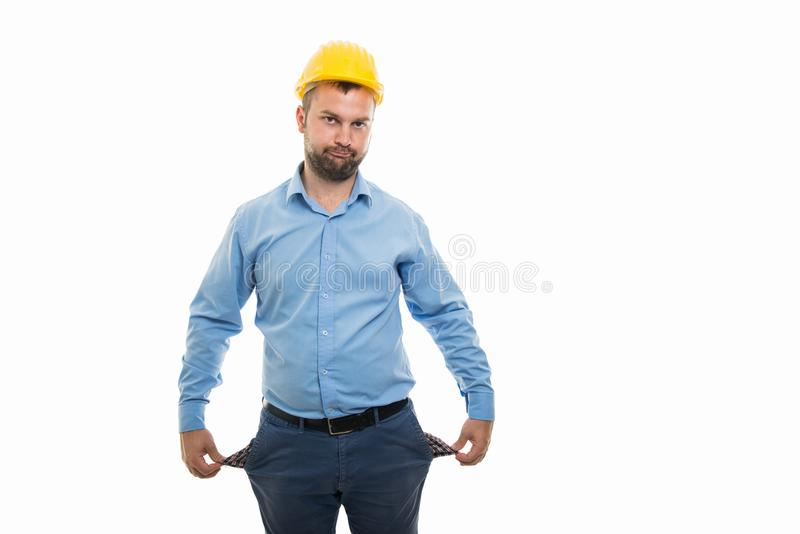 Junger Architekt mit dem gelben Sturzhelm, der leere Taschen zeigt, gestikulieren stockbild