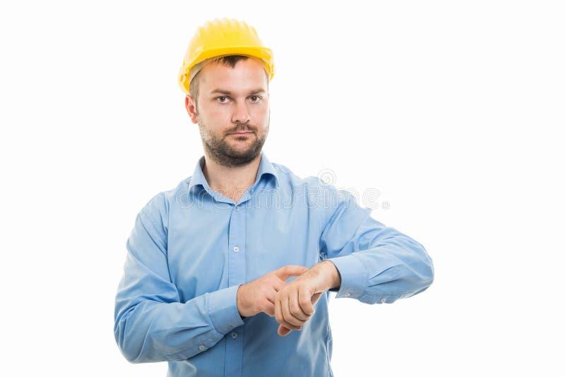 Junger Architekt mit dem gelben Sturzhelm, der späte Geste zeigt stockfotografie