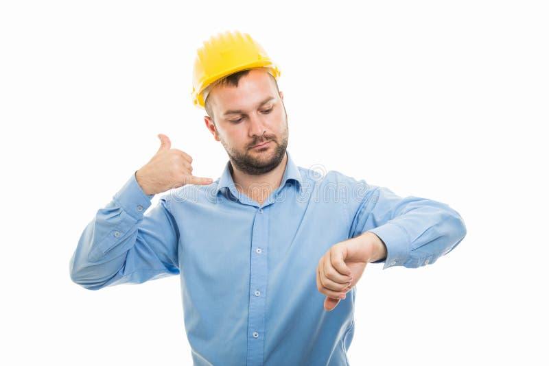 Junger Architekt mit dem gelben Sturzhelm, der Telefonzusammenkunft gest festlegt lizenzfreies stockfoto