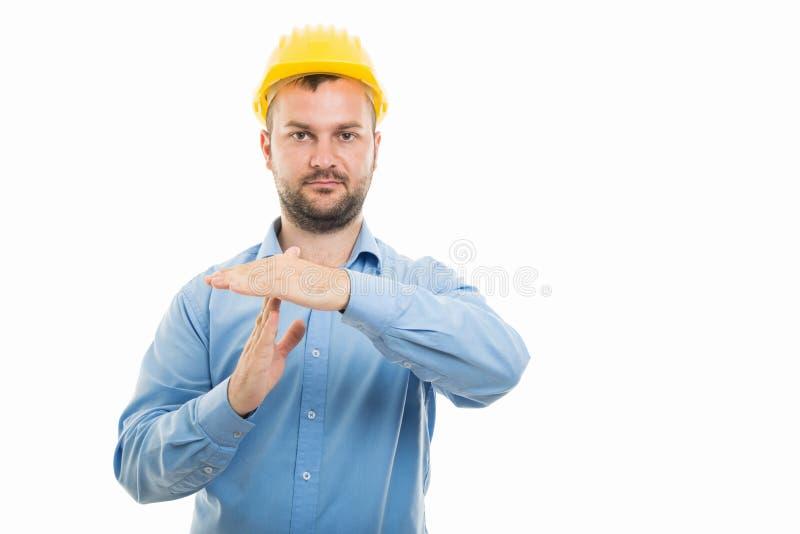 Junger Architekt mit dem gelben Sturzhelm, der Zeit heraus zeigt, gestikulieren stockfoto