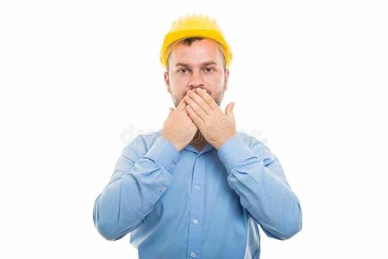 Junger Architekt mit gelbem Sturzhelmbedeckungsmund stockbild