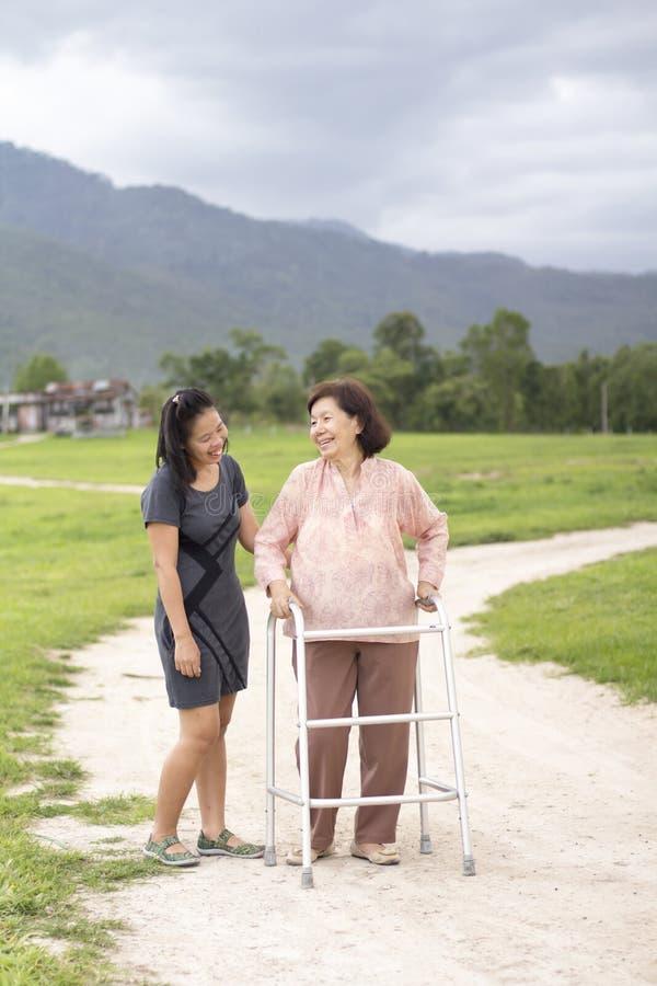 Junger Asiat mach's gut die ältere Frau mit Wanderer im Bauernhof lizenzfreie stockfotos