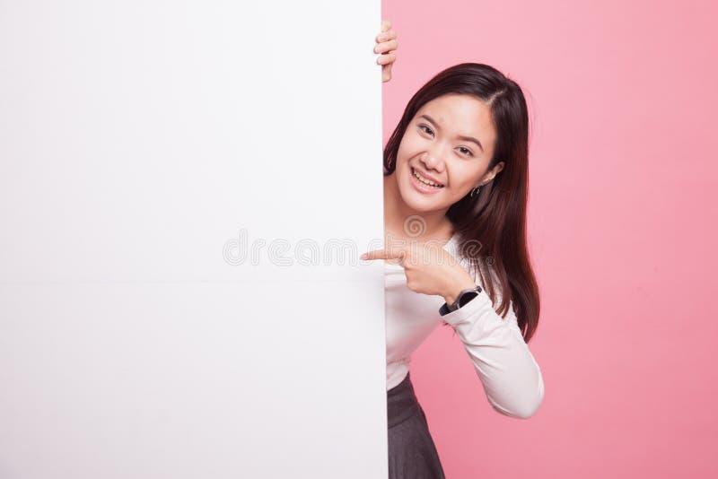 Junger Asiatinpunkt zu einem leeren Zeichen stockfotos