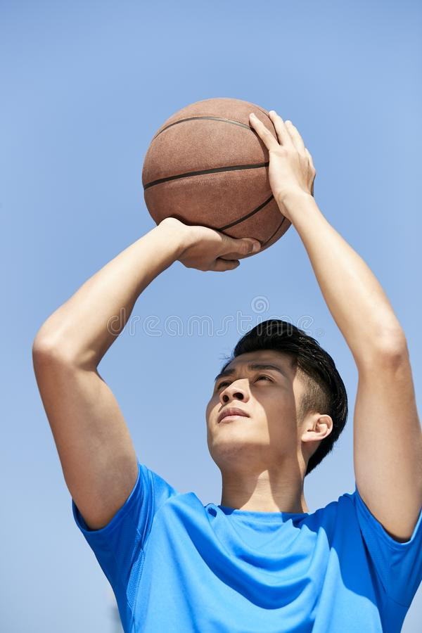 Junger asiatischer Basketball-Spieler, der Jump-Shot macht lizenzfreies stockbild