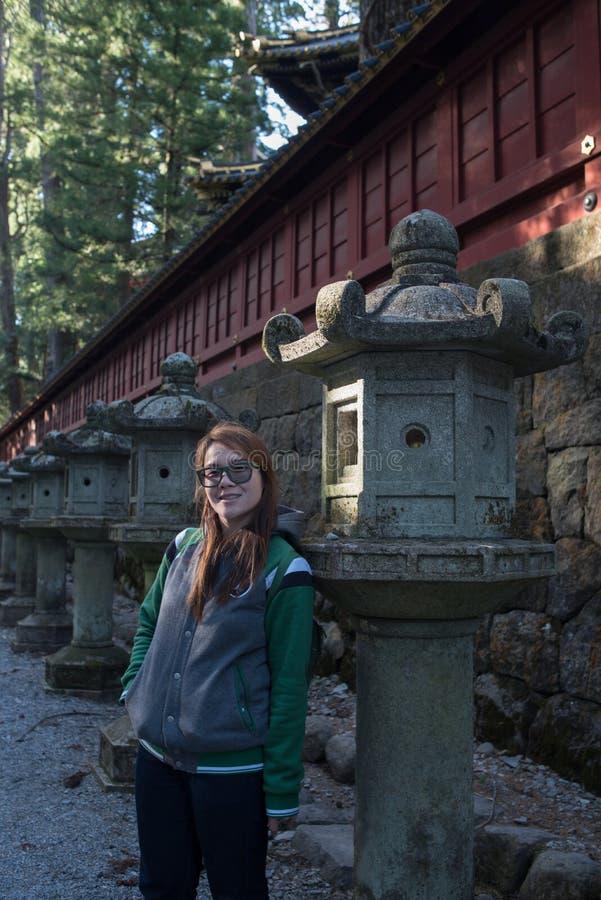 Junger asiatischer Damenstand nahe bei altem Pfosten in Nikko lizenzfreies stockfoto