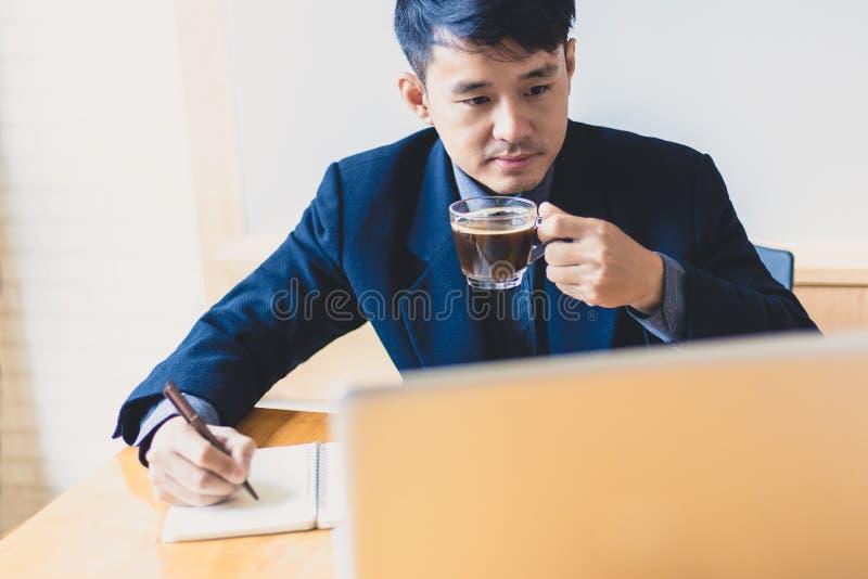 Junger asiatischer Exekutivgeschäftsmann, der eine Anmerkung schreibt und compu verwendet stockfoto