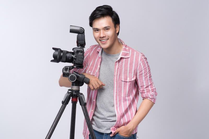 Junger asiatischer Fotograf, der Digitalkamera, beim Arbeits i hält stockfoto