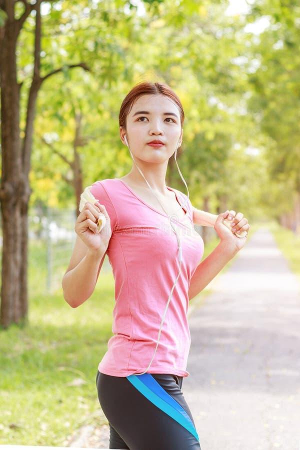 Junger asiatischer Frauenläufer, der für das Rütteln sich vorbereitet lizenzfreie stockfotos