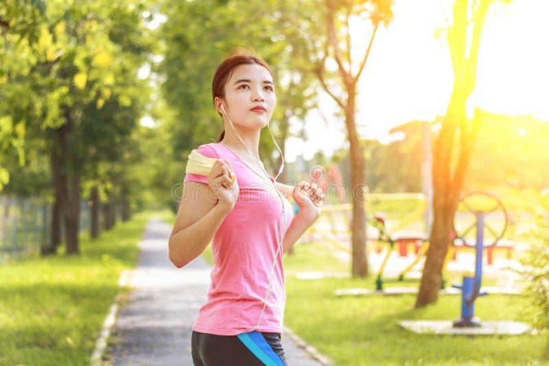Junger asiatischer Frauenläufer, der für das Rütteln sich vorbereitet lizenzfreies stockbild