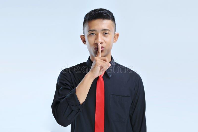 Junger asiatischer Geschäftsmann, der bittet, mit dem Finger auf Lippen ruhig zu sein Ruhe- und Geheimniskonzept lizenzfreies stockbild