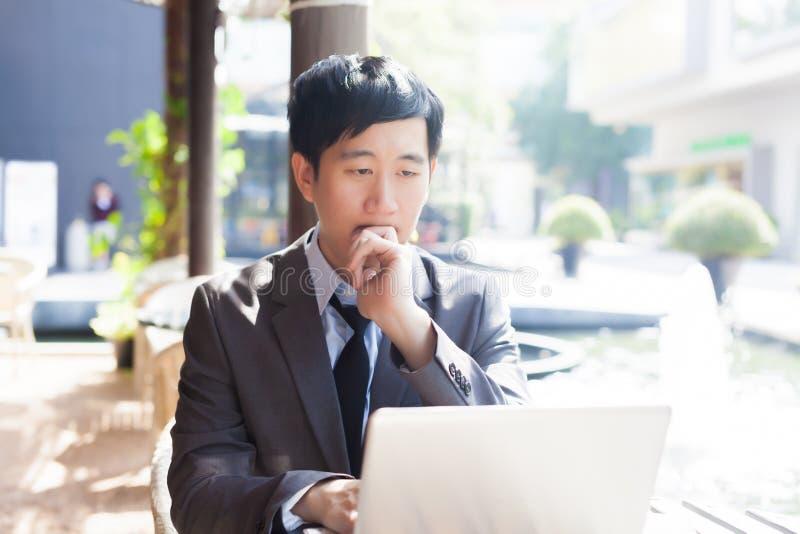 Junger asiatischer Geschäftsmann, der mit seinem Laptop Szene in der im Freien arbeitet stockbilder