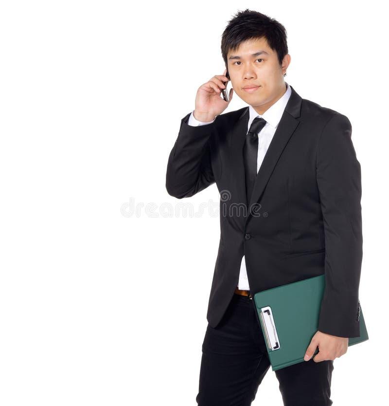 Junger asiatischer Geschäftsmann mit Datei und Telefon stockfotos