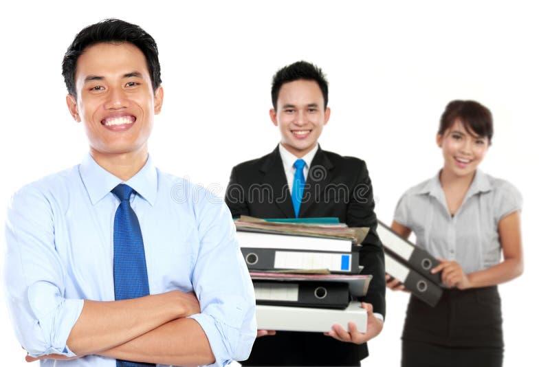 Junger asiatischer Geschäftsmann, mit seinem Team hinten Lokalisiert im Weiß lizenzfreies stockfoto