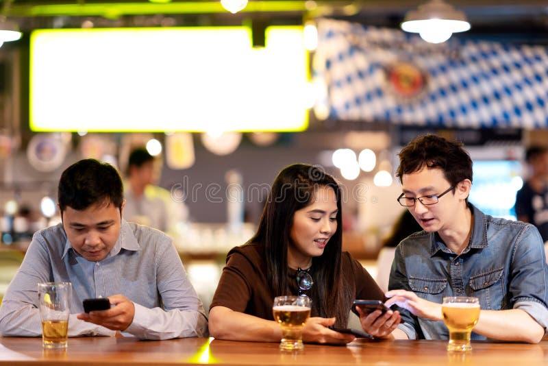 Junger asiatischer Geschäftsmann und Frau oder Freiberufler, die an trinkendem Bier der Nachtklubbar unter Verwendung des Smartph stockfotos