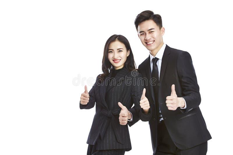 Junger asiatischer Geschäftsmann und Geschäftsfrau, welche die Zweidaumen zeigt lizenzfreie stockbilder