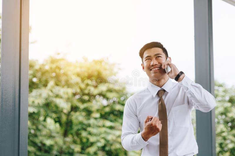Junger asiatischer hübscher Geschäftsmann, der auf Telefon und Glück spricht stockbild