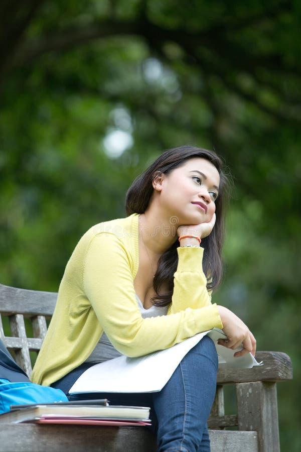 Junger asiatischer Hochschulstudent, der auf Holzbank im Park sitzt lizenzfreies stockfoto