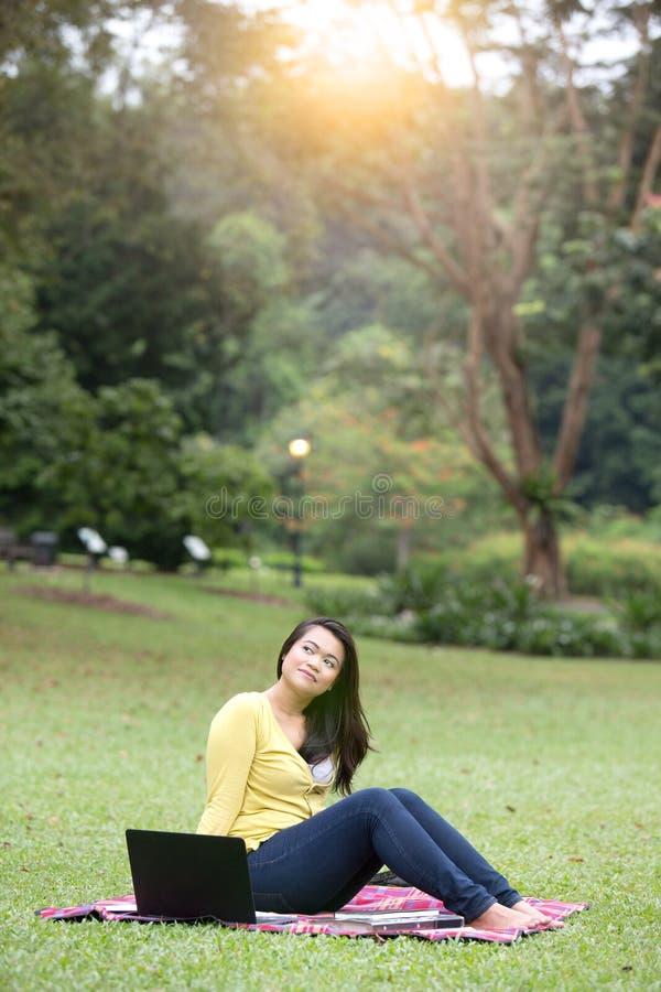 Junger asiatischer Hochschulstudent, der im Park sitzt stockfotos