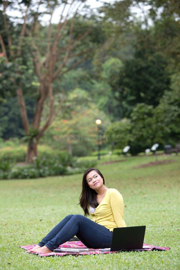 Junger asiatischer Hochschulstudent, der im Park sitzt stockbild
