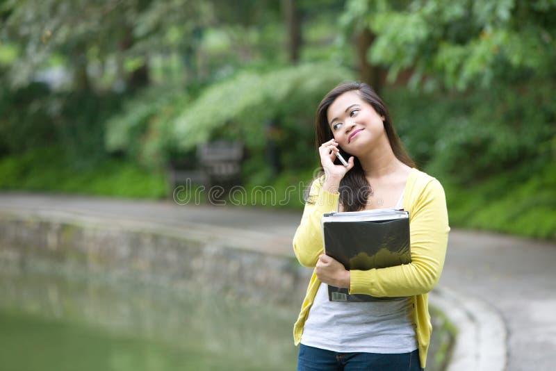 Junger asiatischer Hochschulstudent am Telefon im Park stockfotografie