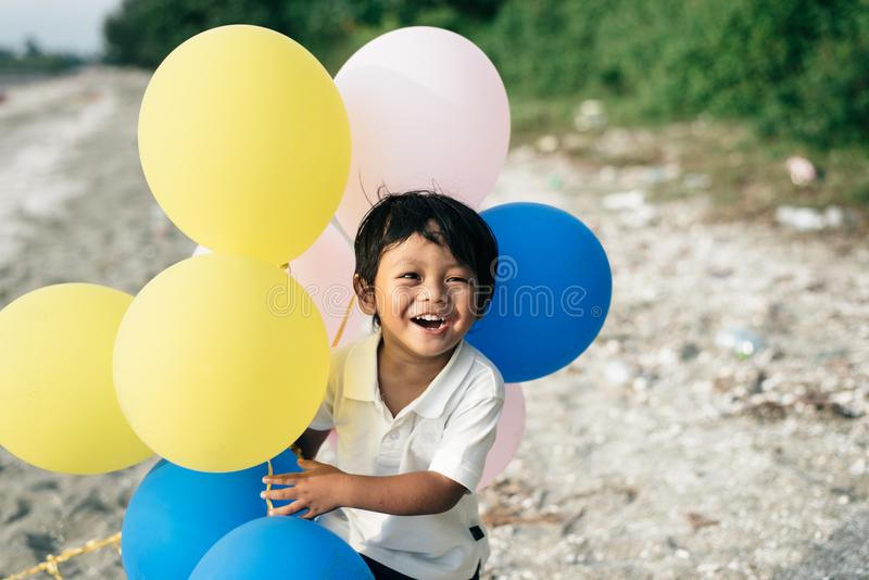 Junger asiatischer Junge, der beim Halten von Ballonen lächelt und lacht stockbild