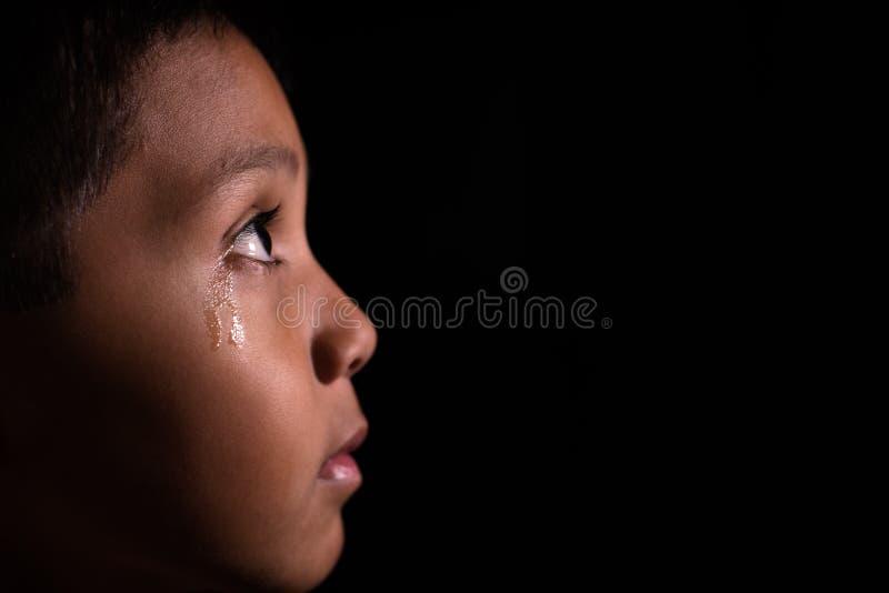 Junger asiatischer Junge, der Licht in der Dunkelheit mit Tränen in seinem Auge untersucht lizenzfreies stockbild