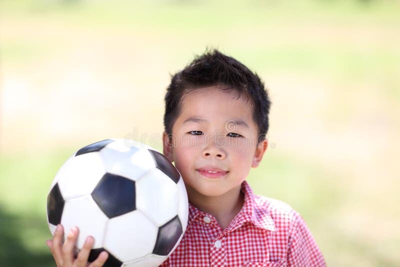 Junger asiatischer Junge mit Fußball lizenzfreie stockfotos