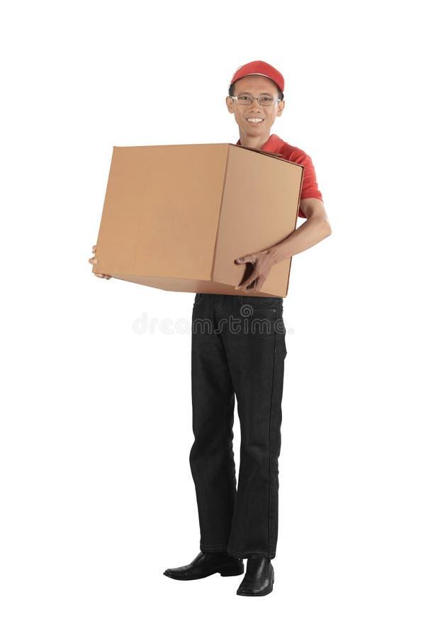 Junger asiatischer Lieferer, der einen großen Paketkasten trägt lizenzfreies stockfoto