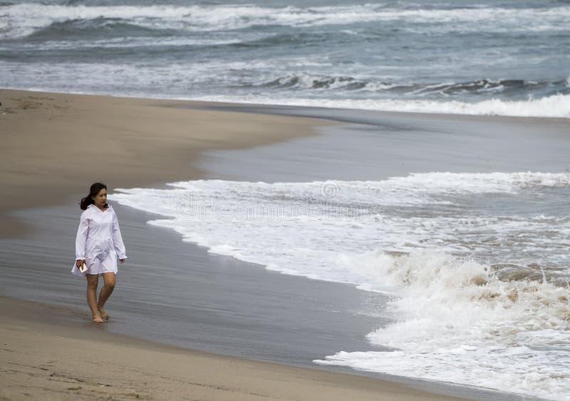 Junger asiatischer Mädchenspaziergang am Strand lizenzfreie stockbilder