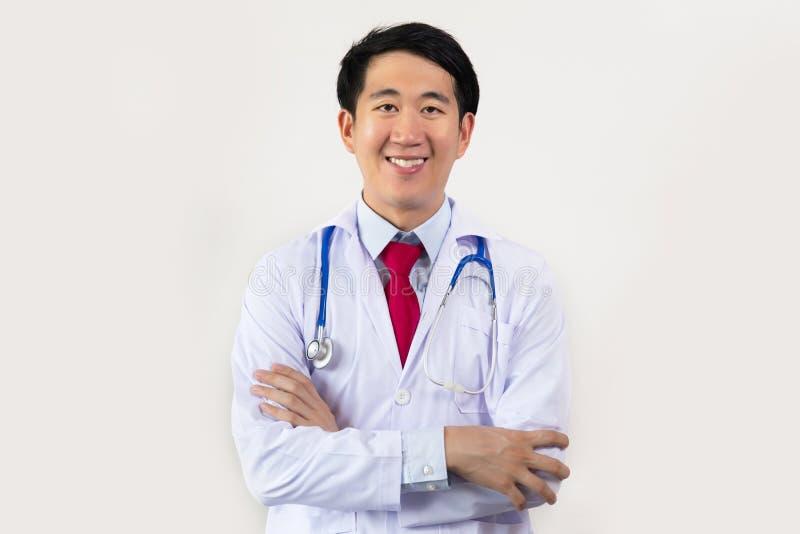 Junger asiatischer männlicher Doktor, der mit den Armen lächelt, faltete Haben des Stethoskops auf seinem Hals, der auf weißem Hi stockfotos